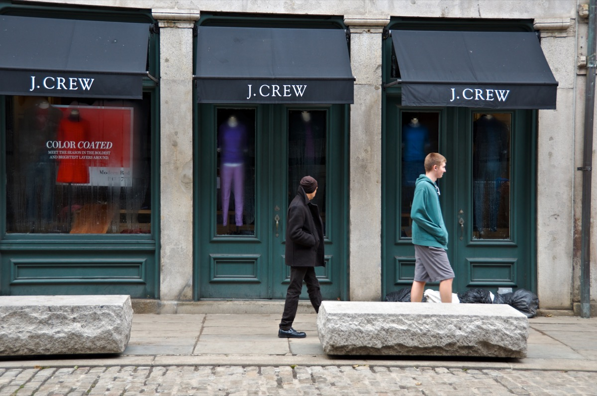 """""""New York City, USA - October 31, 2012: In the aftermath of Hurricane Sandy two men walk past the J. Crew store along Fulton Street in the water and wind damaged retail area in the South Street Seaport district in Lower Manhattan."""""""