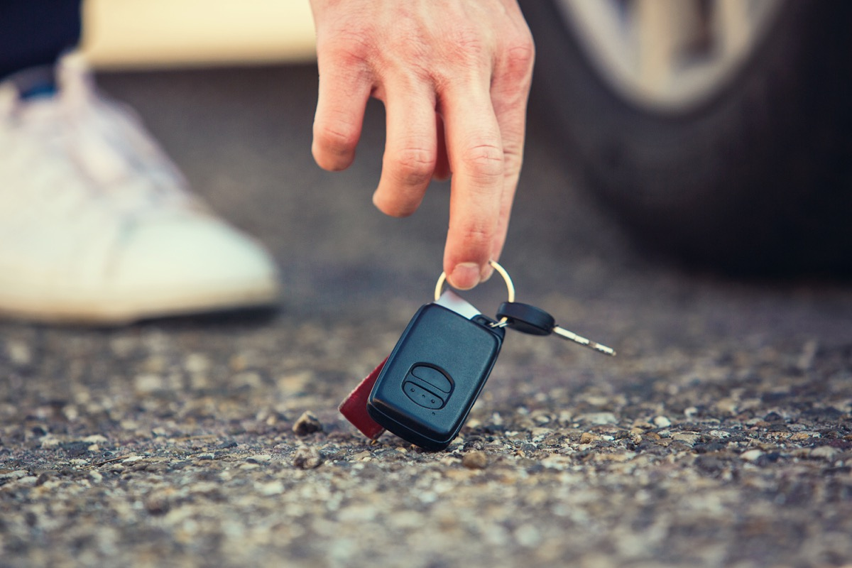 Close up of man hand lifting car keys fallen on the ground. Guy found vehicle keys someone lost on the asphalt road in the parking. Return property to owner.
