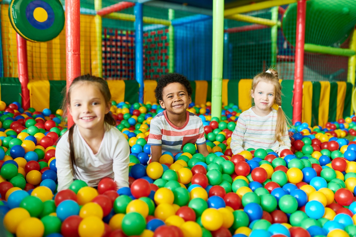 three kids playing in ball pit