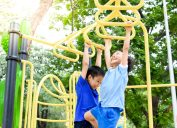 two young boys playing on monkey bars