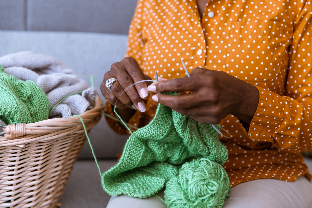 senior sitting on the couch and knitting at home