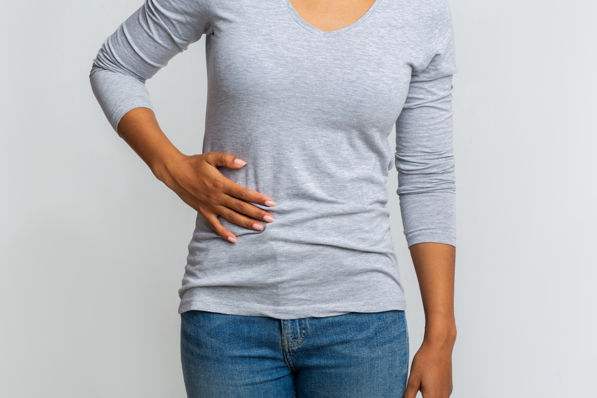 Cropped of girl holding her side, suffering from acute liver pain, grey background