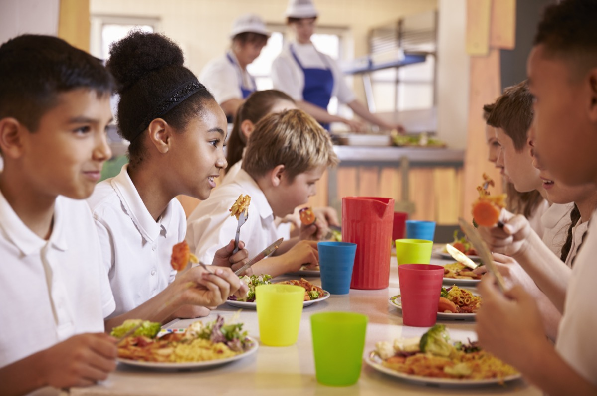 Kids eating lunch together at school in cafeteria