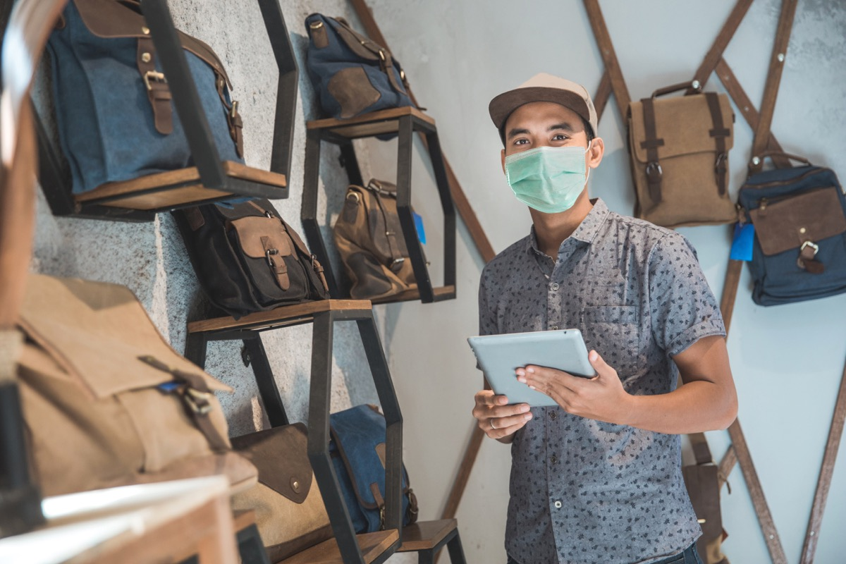 young asian man wearing face mask in backpack store
