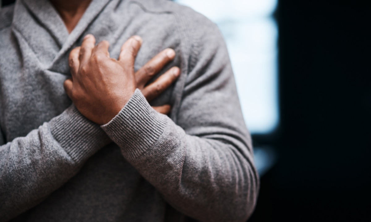 Shot of an unrecongizable man holding his chest in pain indoors