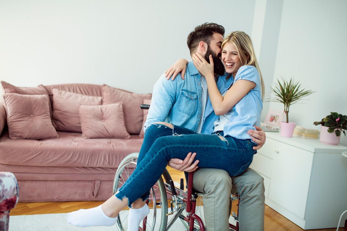 bearded man in wheelchair holding girlfriend on lap