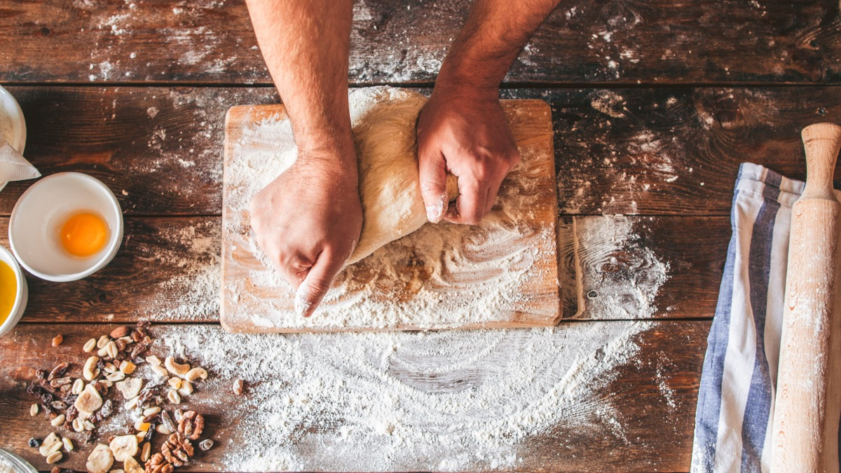 Bakery business. Culinary art. Chef kneading dough. Top view of hands working. Rolling pin and flour on wooden table.
