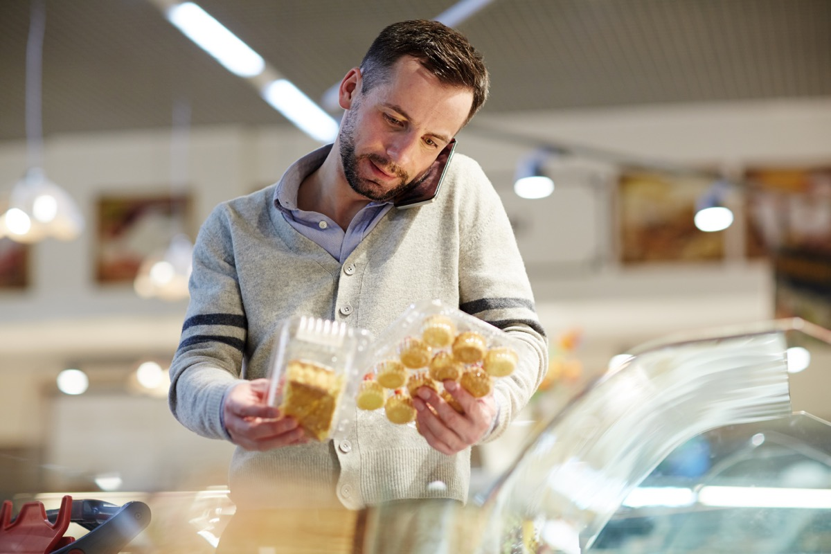 Portrait of confused middle-aged man doing grocery shopping in supermarket: calling his wife asking what dessert to choose