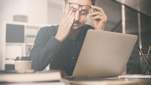 Tired young man rubbing his eyes in front of a computer