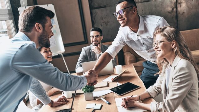 30-something white guy and black guy shaking hands over table in meeting at work