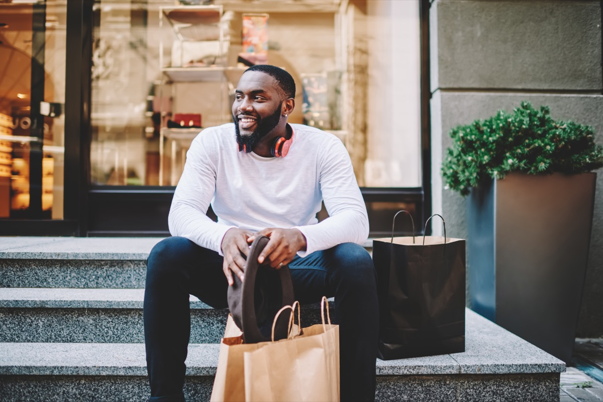 Smiling male customer in trendy wear sitting on stairs of store with bags with copy space for label, cheerful dark skinned hipster guy recreating after shopping and buying purchases
