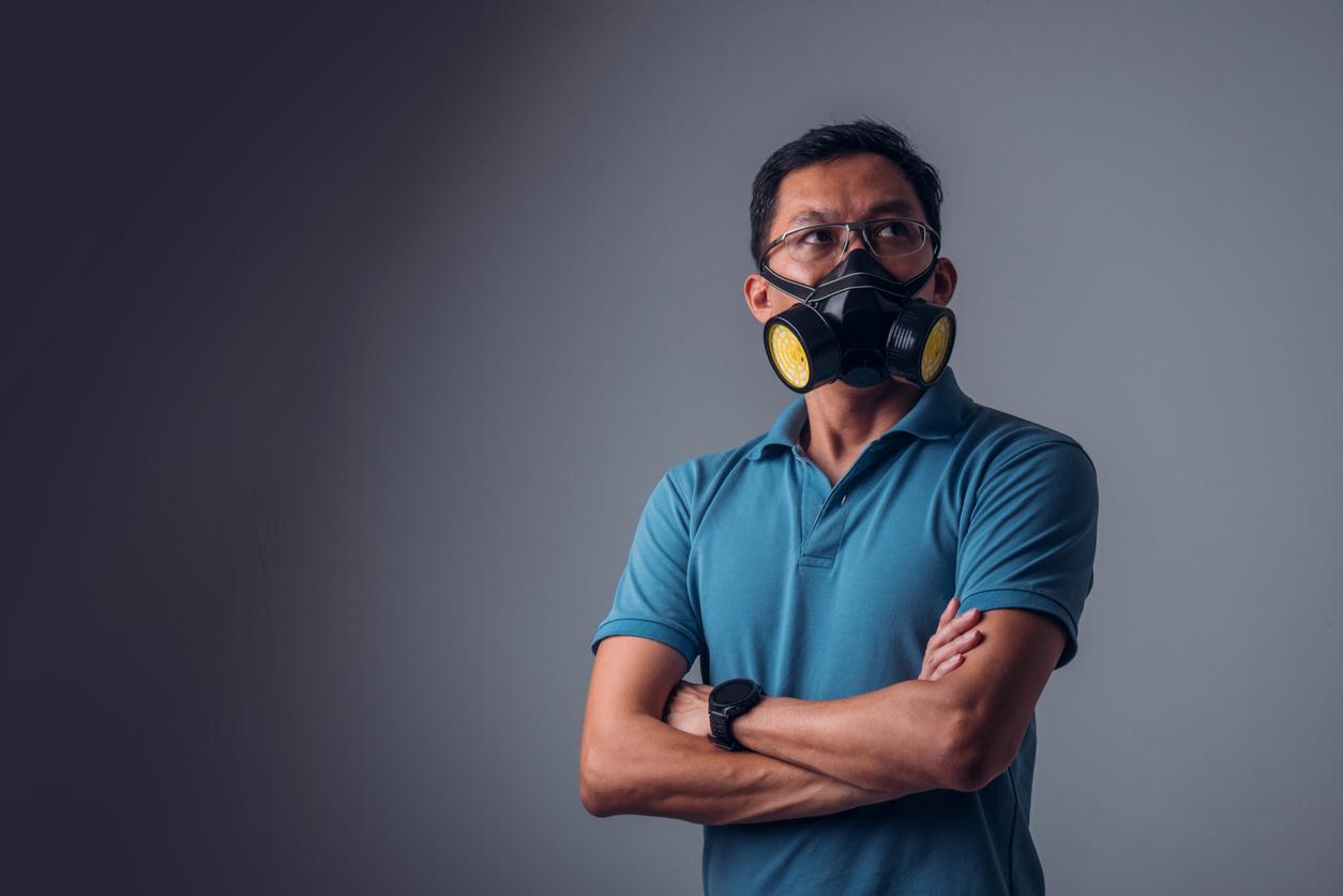 asian man in a blue collared shirt wearing an elastomeric mask