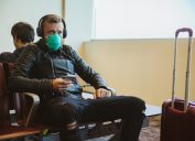 young white man sitting at airport wearing face mask