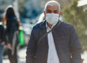 Senior Men covering his face with pollution mask for protection from viruses
