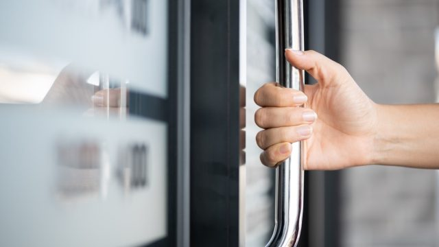 Closeup woman hand holding the door bar to open the door with glass reflection background.