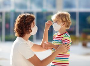 Mother putting a mask on her child
