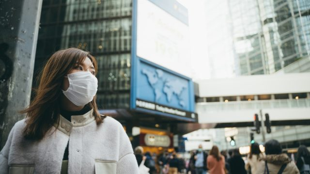 Young Asian woman wearing a protective face mask to prevent the spread of germs and viruses in the city