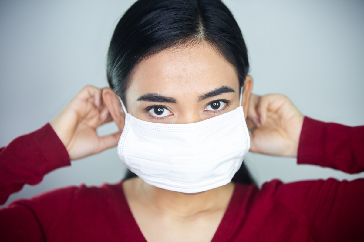 Woman making sure mask is comfortable before wearing