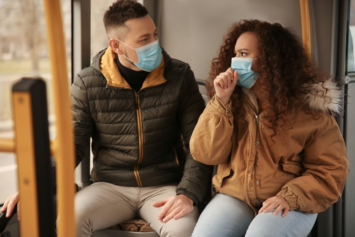 Couple wearing masks on public transportation together