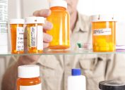 Senior adult man gets prescription medicines out of his medicine cabinet