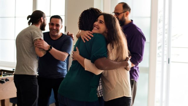group of middle aged friends of different races hugging