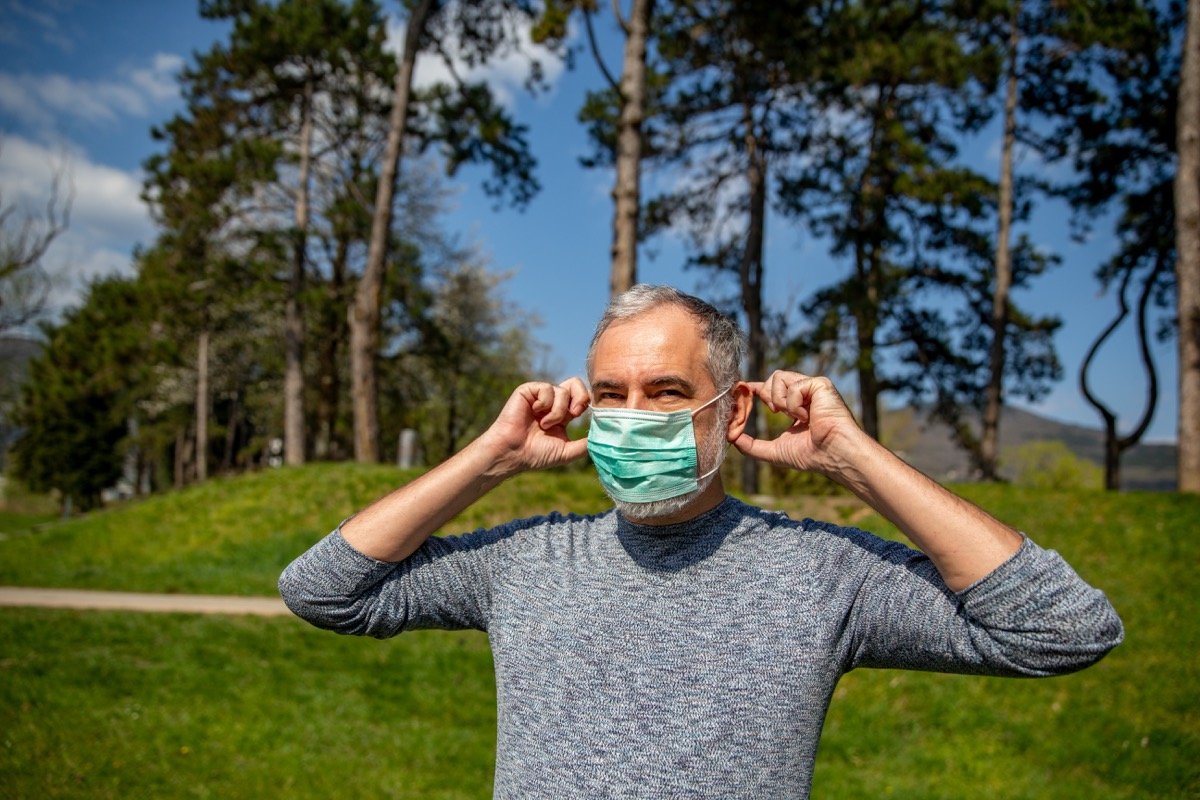 Mature Man Removing Protective Mask From his Face Outdoors in Public Park.