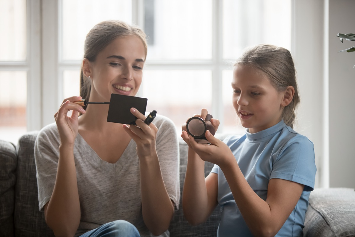 white mom and daughter applying cosmetics