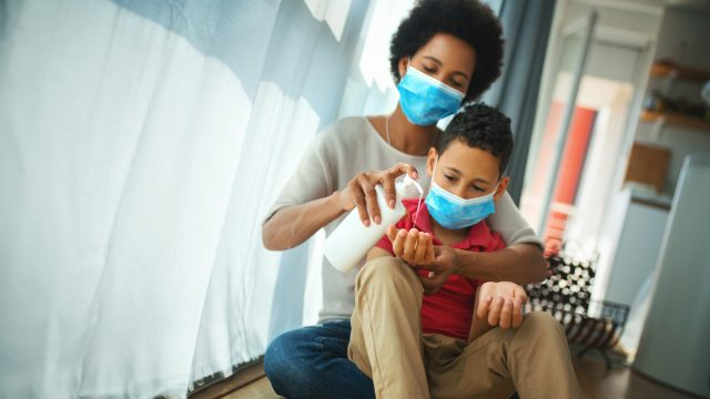 An early 40s black woman with her son, both in masks, staying at home during coronavirus pandemic. The woman is pouring some hand sanitizer into her son's hands