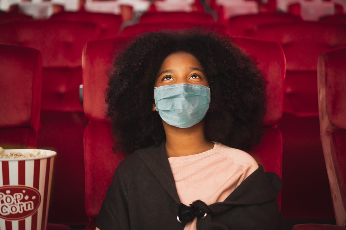 Girl wearing mask in movie theater seat