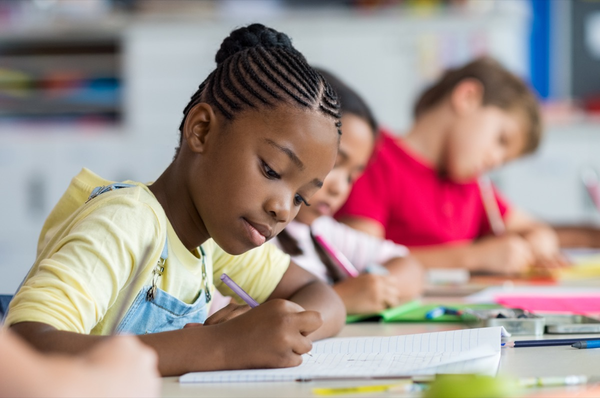 young students writing at desks in school