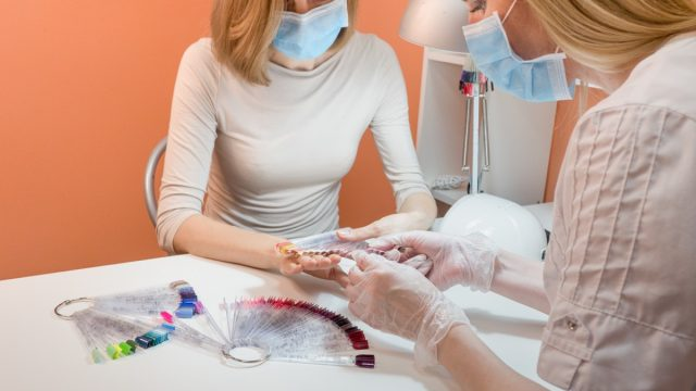 nail salon worker giving manicure wearing face mask