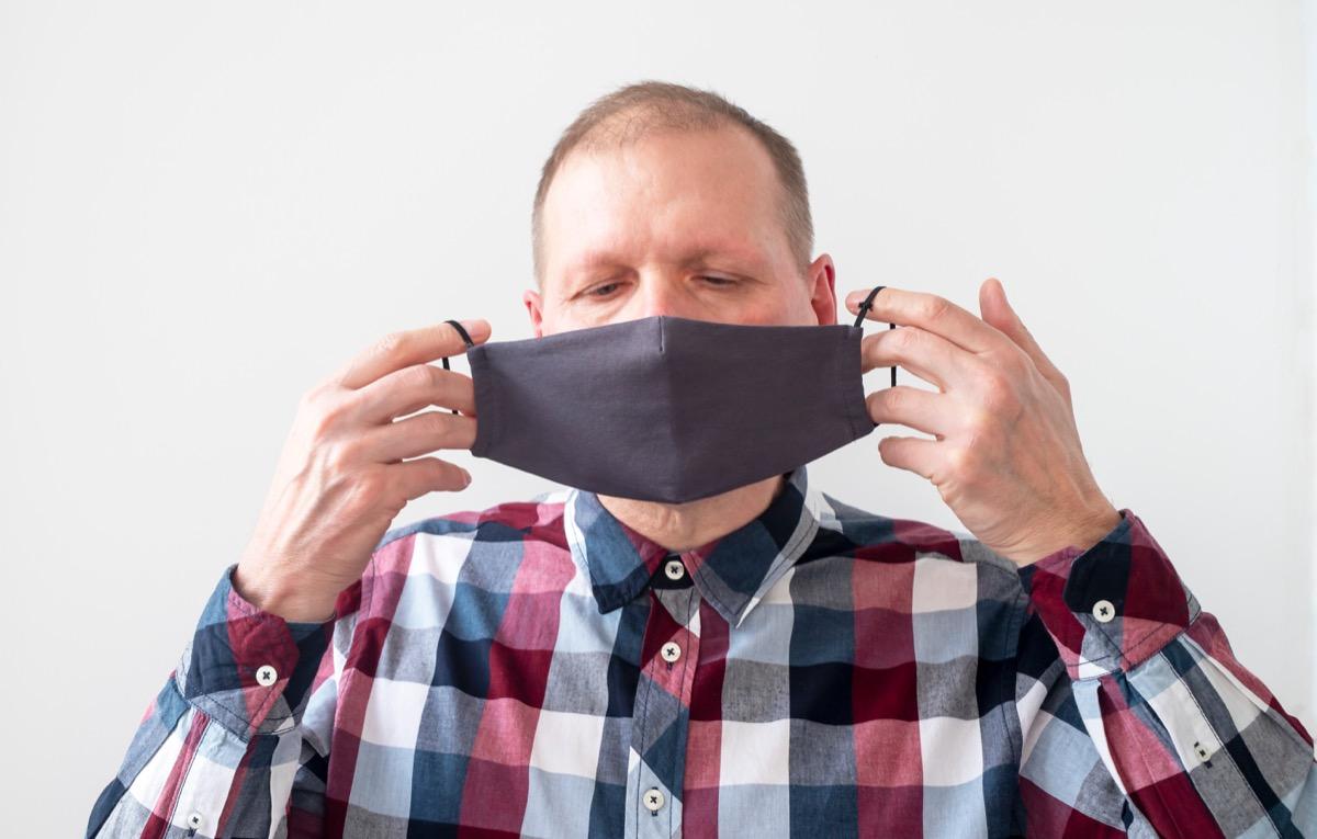 older white man putting on face mask