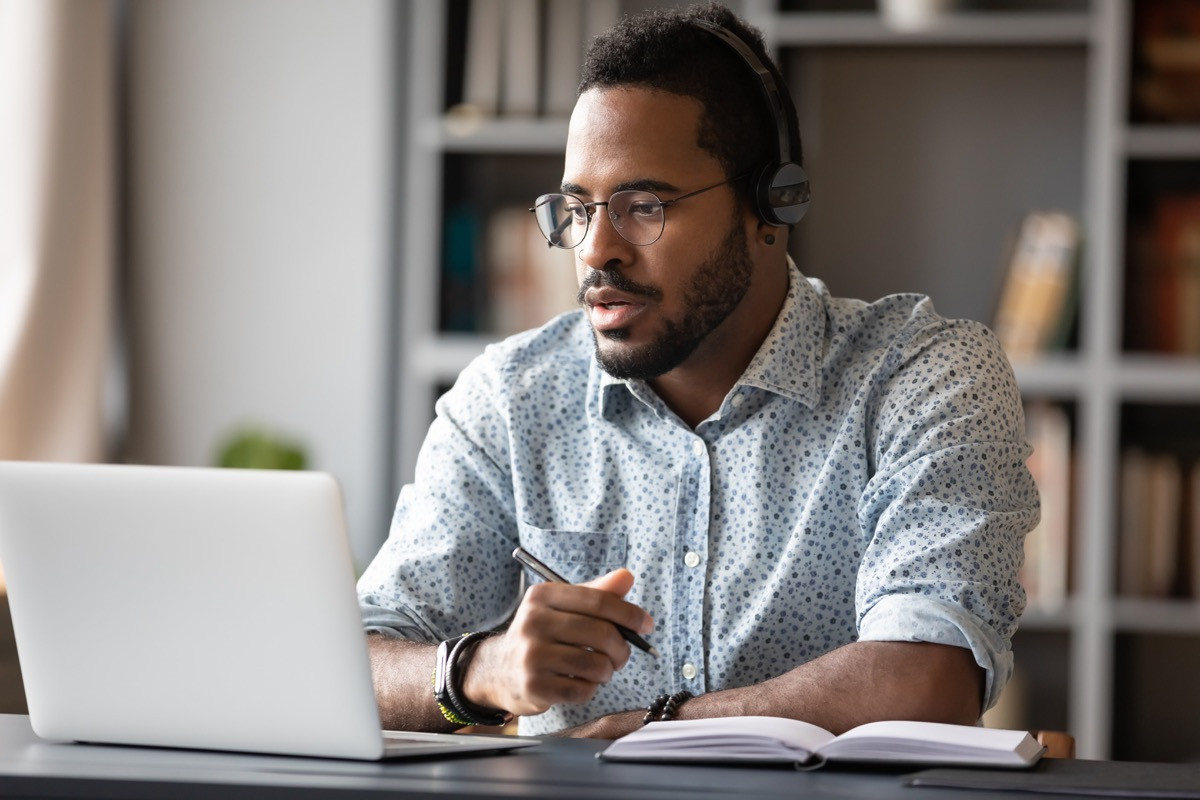 Focused young businessman wear headphones study online watching webinar podcast on laptop listening learning education course conference calling make notes sit at work desk, elearning concept