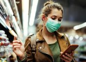 Young woman wearing protective mask on her face and reading shopping list on mobile phone in grocery store during virus pandemic.