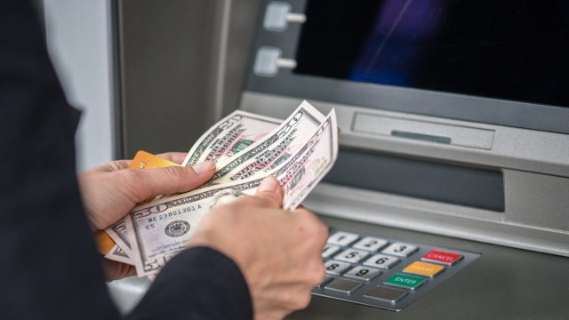 Man counting money in front of cashpoint.