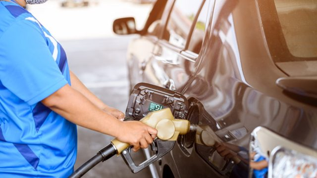 closeup of someone pumping gas at gas station