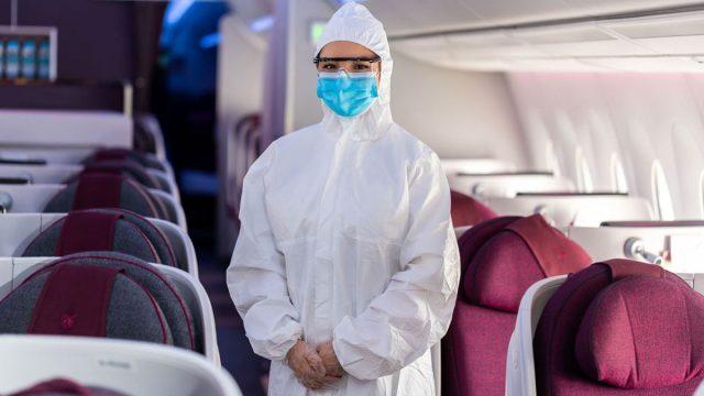 flight attendant wears a hazmat suit in an airplane