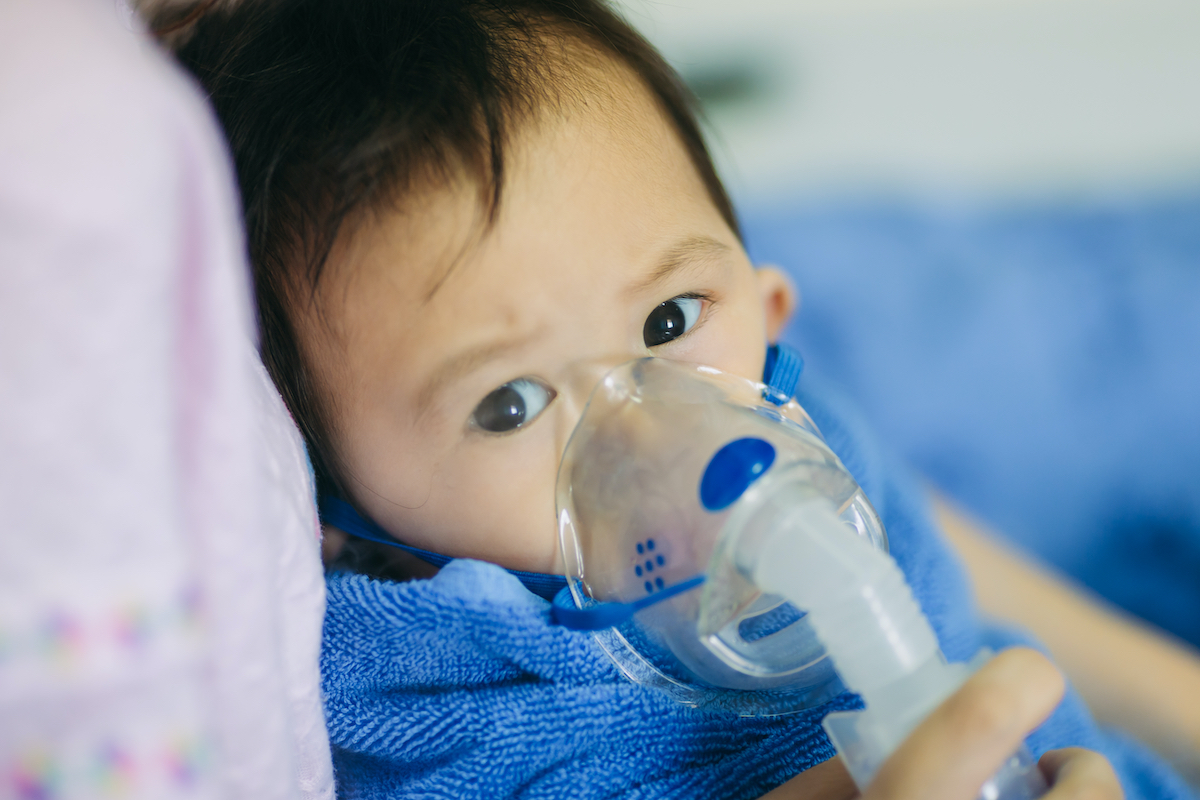 young asian child with respirator