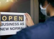 A man wearing a mask puts up an open sign that says business as new normal
