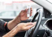 Man using hand sanitizer while sitting in car