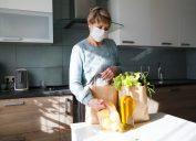 senior woman wearing a mask puts away groceries