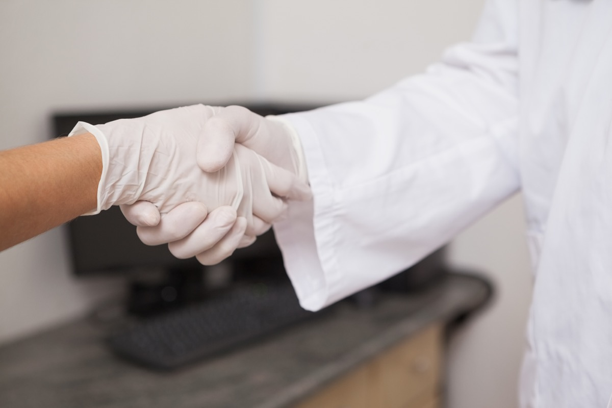 two people shaking hands while wearing gloves