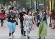 a group of people in masks walk on main street in shanghai disneyland