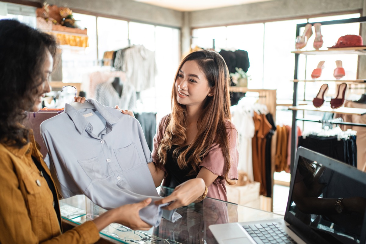 young asian woman returning shirt to store clerk