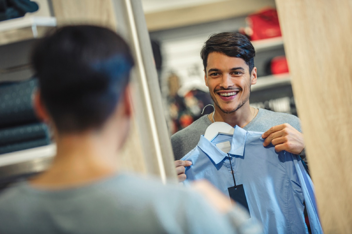 young man looking at shirt in dressing room mirror and smiling
