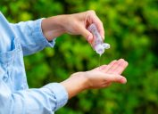 close up of man using hand sanitizer outside