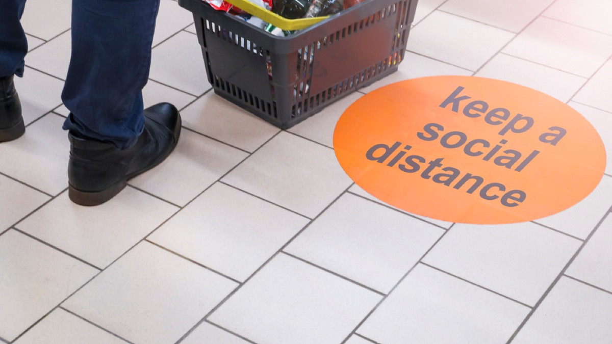 close up of sign on the floor saying keep a social distance