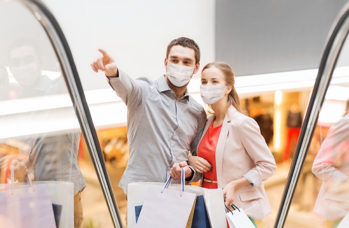 white man and woman wearing face masks going up a mall escalator
