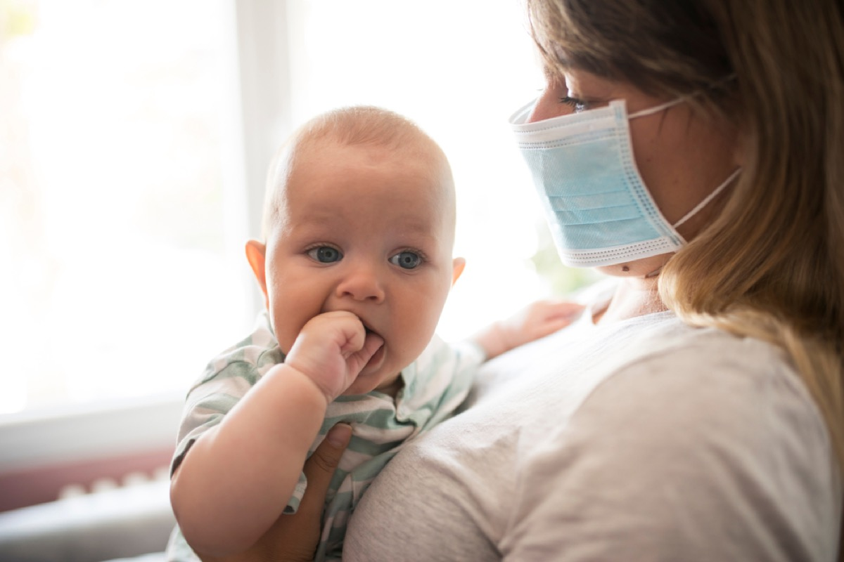 baby with mother wearing face mask