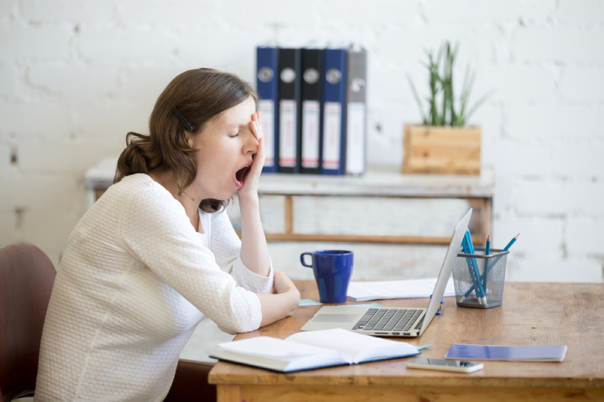 young white woman yawning at her desk in front of a laptop